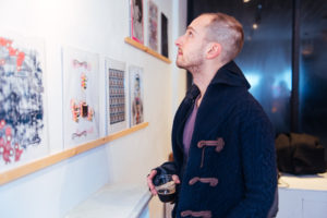 Composer Trevor Bachman looking at risograph prints at Drums on Paper III, Ground Floor Gallery, Park Slope, Brooklyn